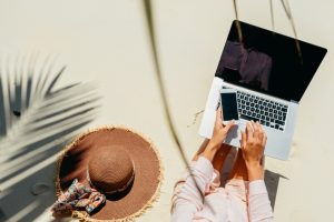 woman-freelancer-travel-and-working-on-the-beach-working-remotely-on-the-laptop-computer
